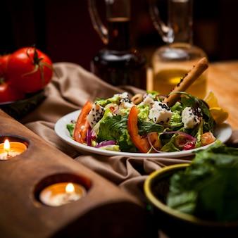 Insalata greca di vista laterale con le candele e pomodoro e verdi in piatto bianco rotondo