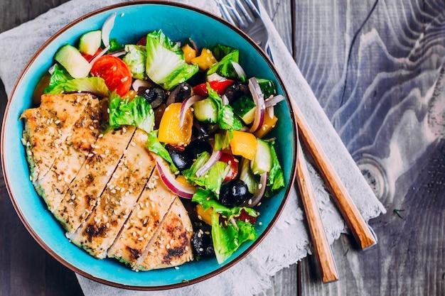 Insalata greca e pollo arrostito in piatto sulla tavola di legno. vista dall'alto con spazio di copia