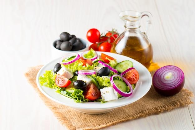 Insalata greca fresca a base di pomodorini, rucola, rucola, feta, olive, cetrioli, cipolla e spezie.