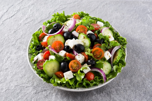 Insalata greca fresca nel piatto con olive nere, pomodoro, formaggio feta, cetriolo e cipolla su sfondo grigio