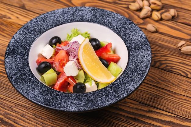 Insalata greca saporita con feta, olive e pomodori in una ciotola sulla tavola di legno.