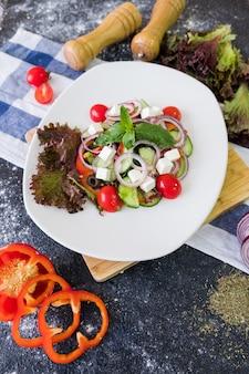 Insalata greca su un piatto bianco su priorità bassa di pietra scura.