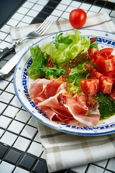 Insalata italiana deliziosa con il prosciutto di parma, la salsa di pesto, la lattuga ed i pomodori ciliegia su un bello piatto ceramico sulla tavola bianca. vista da vicino sul cibo