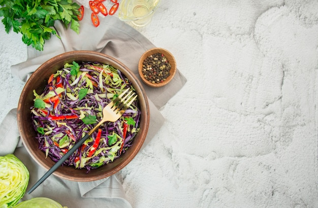 Insalata luminosa di cavolo viola, cavolo bianco, peperone dolce in un piatto su un tavolo leggero. insalata luminosa di verdure fresche. sfondo di cibo. piatto vegetariano. vista dall'alto copia spazio