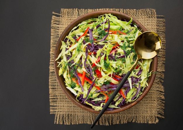 Insalata luminosa di cavolo viola, cavolo bianco, peperone dolce in un piatto su un tavolo scuro. insalata luminosa di verdure fresche. sfondo di cibo. piatto vegetariano. vista dall'alto copia spazio