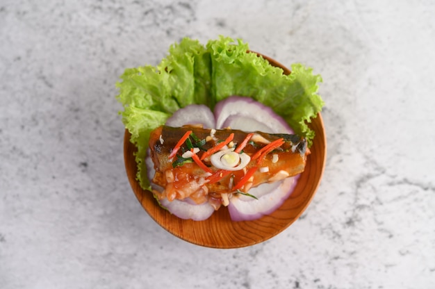 Insalata piccante appetitosa di sardine in scatola con salsa piccante in ciotola di legno