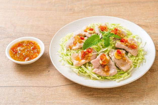 Insalata piccante di maiale o maiale bollito con aglio lime e salsa chili