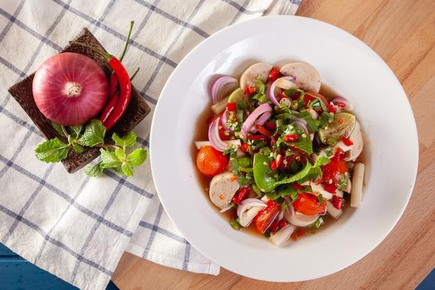 Insalata piccante piccante con tuorlo d'uovo e salsiccia vietnamita con verdure tailandesi