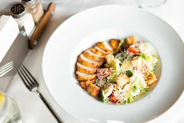 Insalata romain con pollo alla griglia, crostini all'aglio e parmigiano servita su un piatto bianco su un tavolo con una tovaglia bianca, elettrodomestici e un bicchiere di vino in un ristorante