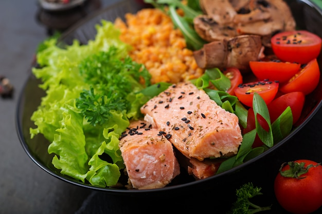 Insalata sana con salmone, pomodori, funghi, lattuga e lenticchie su oscurità