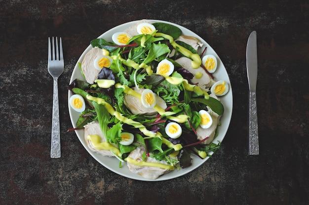 Insalata sana con uova di quaglia, insalata mista e petto di pollo. dieta keto.