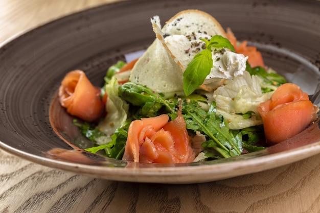 Insalata sana di pesce rosso con foglie di lattuga mista