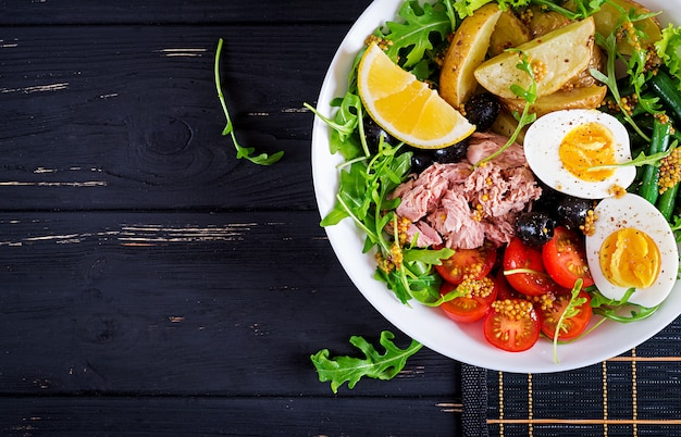 Insalata sana di tonno, fagiolini, pomodori, uova, patate, olive nere close-up in una ciotola sul tavolo.