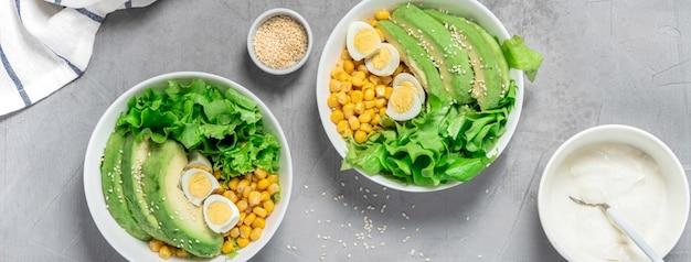 Insalata sana fatta di avocado, lattuga, semi, mais e uova di quaglia in ciotole bianche, vista dall'alto