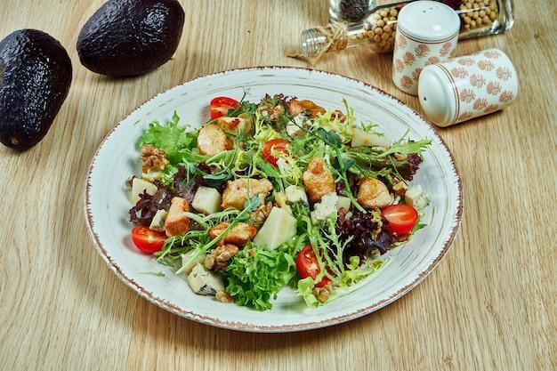 Insalata succosa e verde con formaggio roquefort, lattuga al formaggio blu, semi di sesamo, avocado e pollo teriyaki e pomodorini in una ciotola blu su un tavolo di legno. cibo salutare. nutrizione fitness