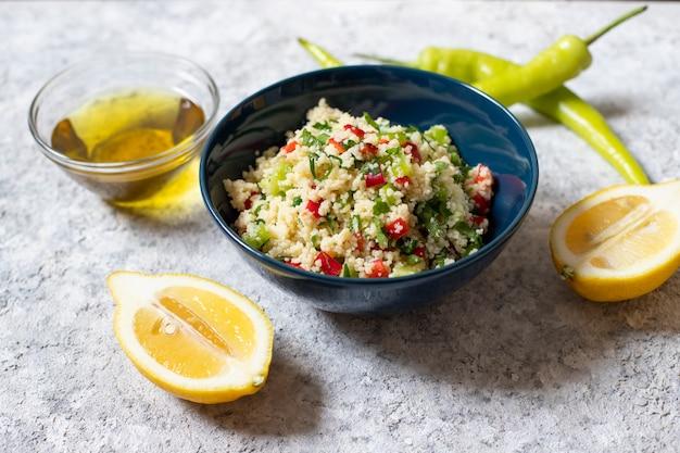 Insalata tabbouleh con cuscus, prezzemolo, limone, pomodoro, olio d'oliva. insalata vegetariana levantina. cucina libanese e araba. sfondo chiaro. vista da vicino