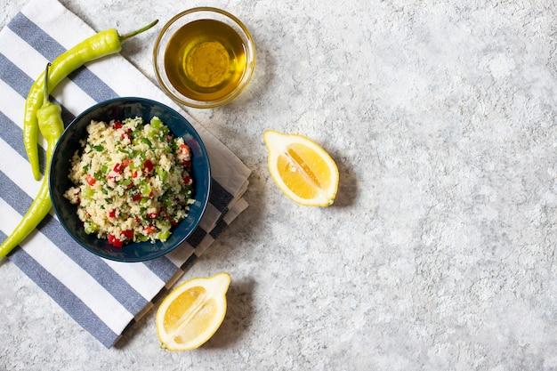 Insalata tabbouleh con cuscus, prezzemolo, limone, pomodoro, olio d'oliva. insalata vegetariana levantina. cucina libanese e araba. sfondo chiaro. vista dall'alto. spazio per il testo