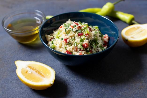 Insalata tabbouleh con cuscus, prezzemolo, limone, pomodoro, olio d'oliva. insalata vegetariana levantina. cucina libanese e araba. sfondo scuro vista da vicino