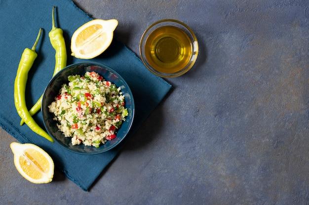 Insalata tabbouleh con cuscus, prezzemolo, limone, pomodoro, olio d'oliva. insalata vegetariana levantina. cucina libanese e araba. sfondo scuro vista dall'alto. spazio per il testo