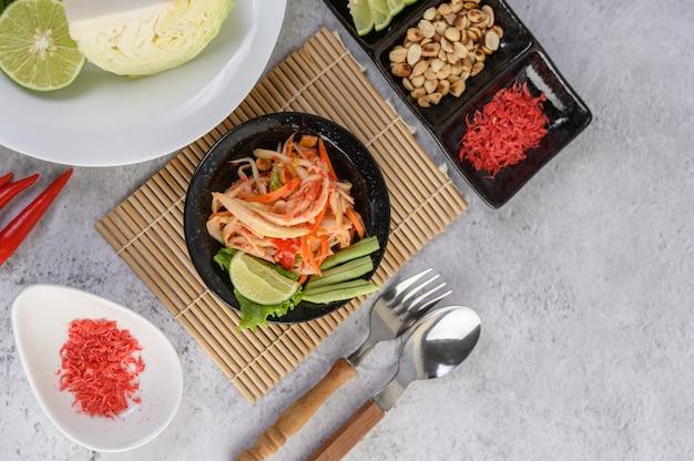Insalata tailandese della papaia in un piatto bianco con riso appiccicoso e gamberetti essiccati