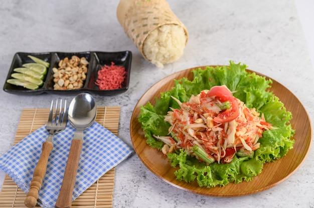 Insalata tailandese della papaia in un piatto di legno con riso appiccicoso e altri ingredienti