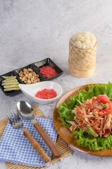 Insalata tailandese della papaia in un piatto di legno con riso appiccicoso