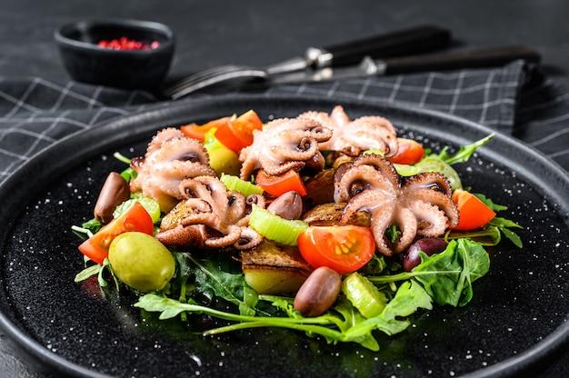 Insalata tiepida con polpo, patate, rucola, pomodori e olive. sfondo nero. vista dall'alto