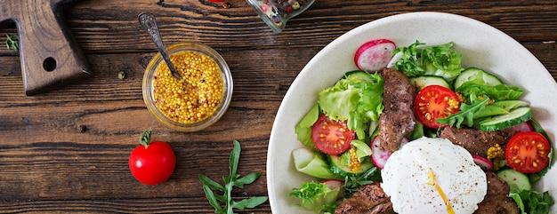 Insalata tiepida di fegato di pollo, ravanello, cetriolo, pomodoro e uovo in camicia. cibo salutare. menu dietetico. vista dall'alto. disteso.