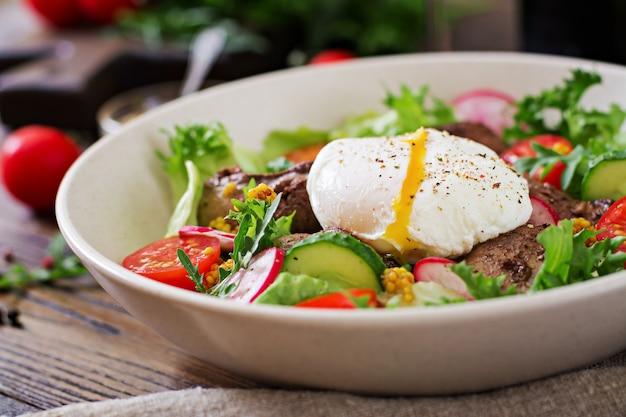 Insalata tiepida di fegato di pollo, ravanello, cetriolo, pomodoro e uovo in camicia. cibo salutare. menu dietetico