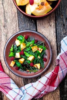 Insalata tiepida di zucca con lamponi e foglie miste di rucola, bietola,