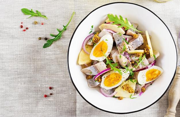 Insalata tradizionale di filetto di aringhe salate, mele fresche, cipolla rossa e uova.
