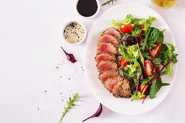 Insalata tradizionale giapponese con pezzi di tonno ahi alla griglia medio-raro e sesamo con insalata di verdure fresche su un piatto