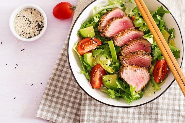 Insalata tradizionale giapponese con pezzi di tonno ahi alla griglia medio-raro e sesamo con verdure fresche su una ciotola.
