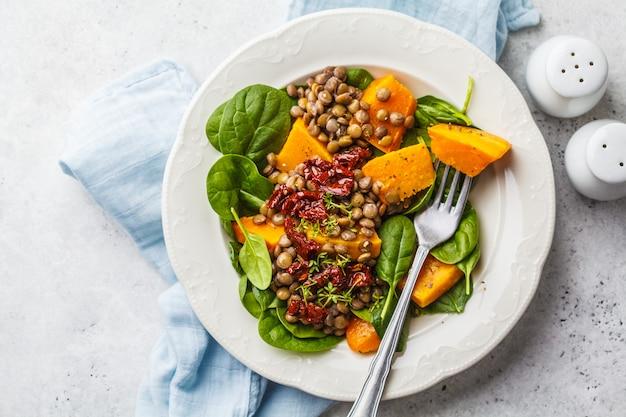 Insalata vegana con lenticchie, zucca e pomodori secchi in zolla bianca.