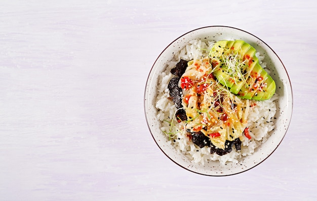 Insalata vegana con riso, cavolo kimchi sottaceto, avocado, nori e sesamo sulla ciotola.
