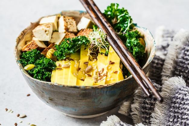 Insalata vegana con tofu affumicato, cavolo nero, avocado e germogli in ciotola,