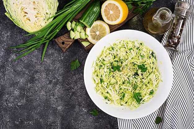 Insalata vegana di primavera con cavolo, cetriolo, cipolla verde e prezzemolo