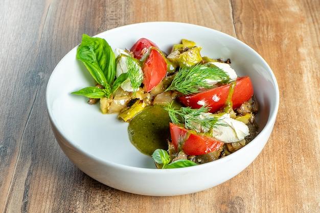 Insalata vegana fresca con verdure al forno in ciotola di whte su fondo di legno. alimento sano ed equilibrato per atleti e dieta.