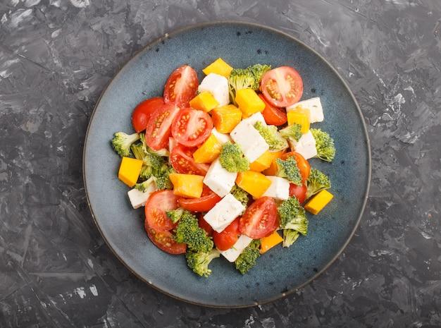 Insalata vegetariana con broccoli, pomodori, formaggio feta e zucca su un piatto di ceramica blu