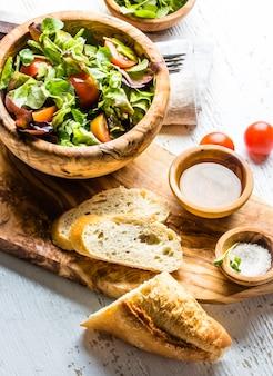 Insalata vegetariana con lattuga e pomodori in ciotola di legno verde oliva