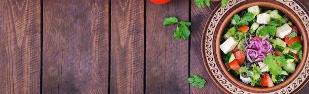 Insalata vegetariana con pomodorini, brie, cetrioli, coriandolo e cipolla rossa. cucina americana. vista dall'alto. disteso. copyspace