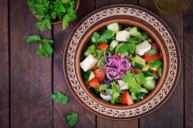Insalata vegetariana con pomodorini, brie, cetrioli, coriandolo e cipolla rossa. cucina americana. vista dall'alto. disteso