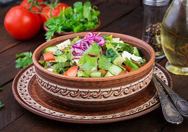 Insalata vegetariana con pomodorini, brie, cetrioli, coriandolo e cipolla rossa. cucina americana.