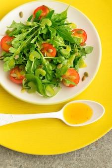Insalata vegetariana con rucola, pomodori ciliegia e semi di girasole sul piatto ceramico bianco, vista superiore