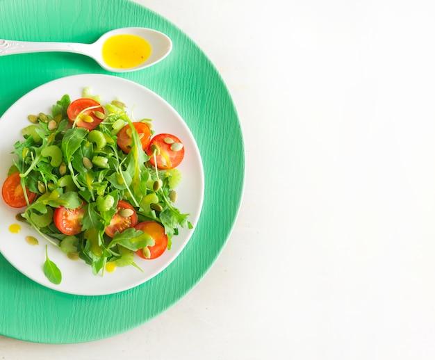 Insalata vegetariana con rucola, pomodorini e semi di girasole sul piatto in ceramica bianca, vista dall'alto, copia spazio