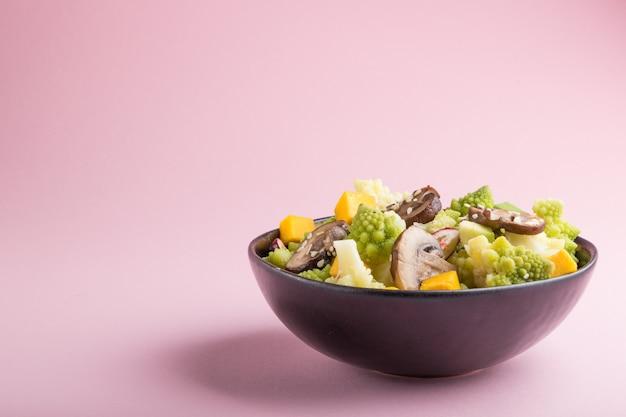 Insalata vegetariana di cavolo romano, funghi prataioli, mirtillo rosso, avocado e zucca su uno sfondo rosa pastello. vista laterale, copia spazio.