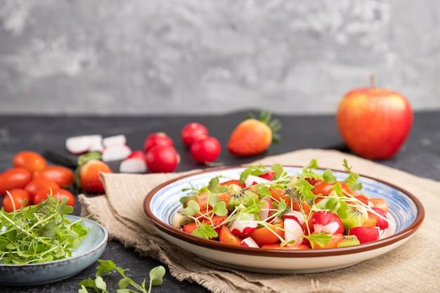 Insalata vegetariana di frutta e verdura di fragole, kiwi, pomodori, germogli microgreen su sfondo nero e grigio e tessuto di lino.