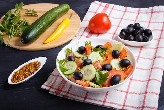 Insalata vegetariana di pomodori, cetrioli, prezzemolo, olive e senape sulla tovaglia di lino.