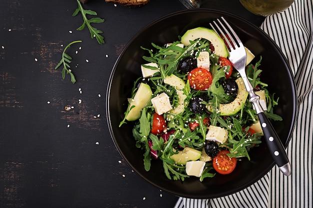 Insalata verde con avocado a fette, pomodorini, olive nere e formaggio