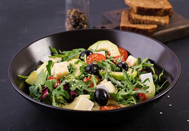 Insalata verde con avocado a fette, pomodorini, olive nere e formaggio.